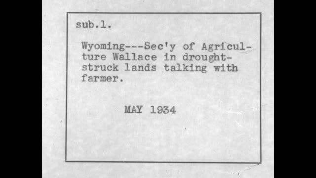 us secretary of agriculture henry wallace walks and talks with farmer and two other men in suits across parched field he stoops and picks up driedup... - dust bowl stock videos and b-roll footage