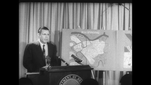 vidéos et rushes de secretary of defense robert mcnamara points to a map of vietnam during a press conference / mcnamara next to a map of haiphong and hanoi where... - press conference