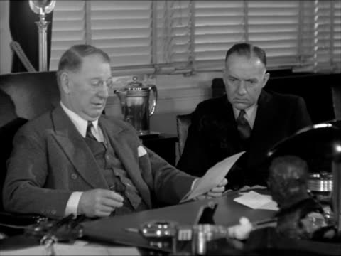 vidéos et rushes de secretary of navy frank knox sitting at desk talking w/ admiral john h towers ms assistant secretary of navy for air artemus l gates frank knox... - 1941