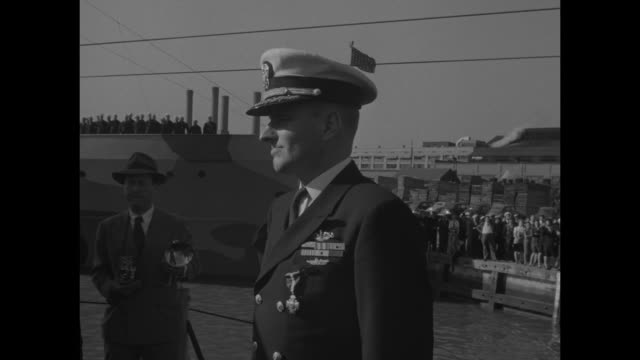 Secretary of Navy James Forrestal stands at attention / VS Lt Commander George Street III at attention wearing various ribbons and the Navy Cross /...