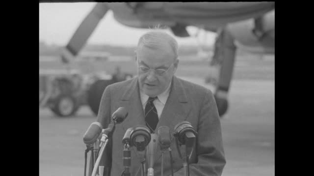 US Secretary of State John Foster Dulles at Washington DC airport upon arrival stands at microphones in front of airplane and speaks to journalists...