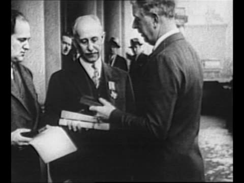 vídeos de stock, filmes e b-roll de us secretary of war dwight f davis pins the distinguished flying cross medal to orville wright's lapel and shakes his hand cu wright with medal on... - orville wright