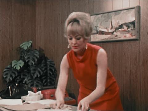 vídeos de stock, filmes e b-roll de 1969 secretary rifling through papers on desk / answering telephone / sitting on desk and talking - fofoca