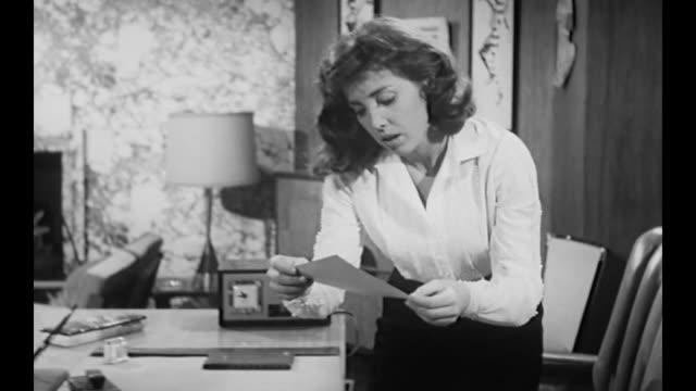 vídeos de stock e filmes b-roll de 1959 secretary steals correspondence from her boss's desk drawer - correspondência