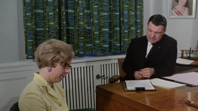 1968 MS Secretary transcribing businessman's dictation / London, England