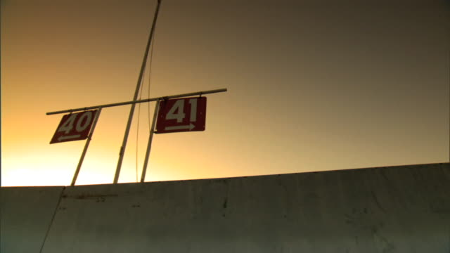 section number signs 40 & 41 hanging from metal bar above stadium top wall, gray to orange sky bg, white sunlight. directional sign, arrow, arrows,... - directional sign stock videos & royalty-free footage
