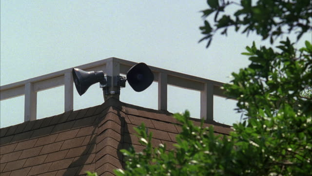 ms section of building with loudspeakers mounted on wall - megaphone stock videos & royalty-free footage