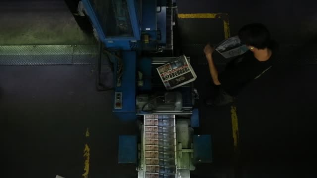 sections of the apple daily newspaper published by next media ltd move along a conveyor as press operators inspect the print quality at the companys... - occupy central stock videos & royalty-free footage