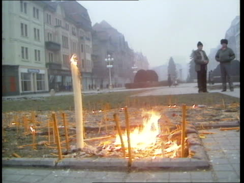 securitate men on trial; itn lib ext candles burning on spot where people were killed - romania点の映像素材/bロール