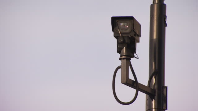 a security camera maintains surveillance from a pole. - pole stock videos and b-roll footage