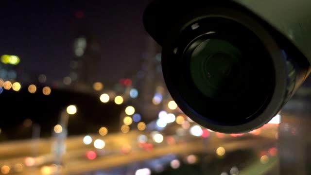 security cctv camera monitoring view of city night - fare la guardia video stock e b–roll