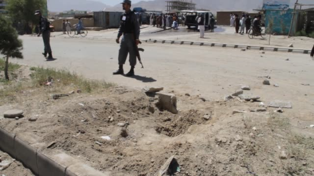 security force members stand guard during the scene investigation and cleaning works at the roadside bomb blast site on the outskirts of kabul... - kabul stock-videos und b-roll-filmmaterial