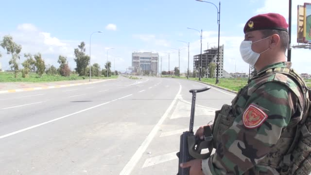 security forces stand guard in erbil city center and various shots of empty streets and closed shops near the citadel of erbil during a curfew... - クルド人点の映像素材/bロール
