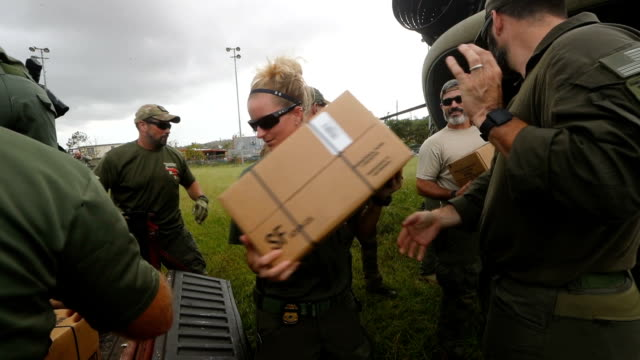 US security forces work delivering aid to an area without electricity and running water more than three weeks after Hurricane Maria hit on October 18...
