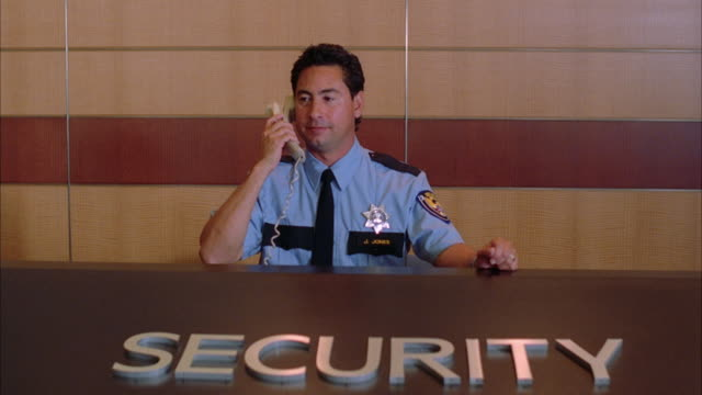A security guard answers the phone at his desk.