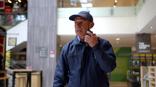 vídeos de stock, filmes e b-roll de segurança do shopping conversando com colegas usando um walkie talkie - sob proteção