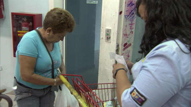 MS PAN Security guard checking customer's receipts before leaving Mission Mercal store / Cabimas, Zulia, Venezuela