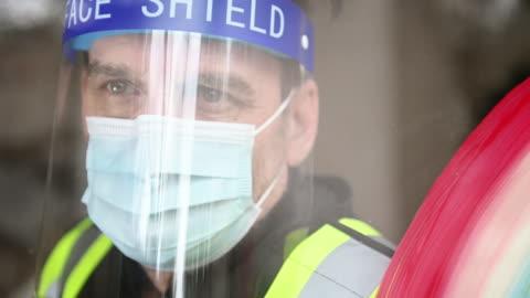 vídeos y material grabado en eventos de stock de guardia de seguridad covid-19 máscara y escudo facial y guantes en y símbolo arco iris - equipo de seguridad