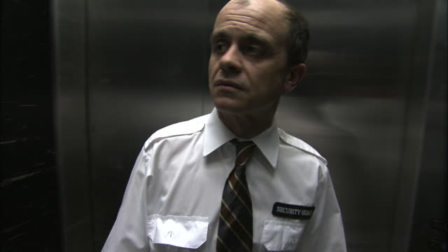 a security guard in an elevator looks around anxiously. - wachmann stock-videos und b-roll-filmmaterial