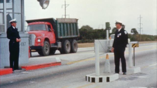 vídeos de stock e filmes b-roll de ms security guard standing at check station - cabina de portagem