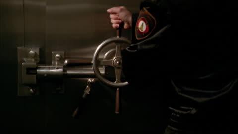 vídeos y material grabado en eventos de stock de a security guard turns a wheel to open the door of a bank vault. - cámara