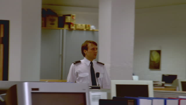 MS PAN Security guard walking through empty office past cubicles / London, England