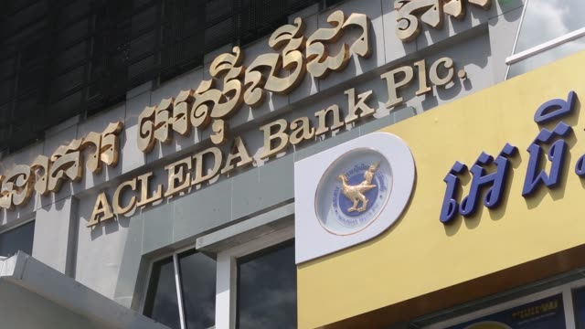 A security guard walks past the Acleda Bank Plc headquarters in Phnom Penh Cambodia on Thursday Sept 15 Signage for Acleda Bank Plc is displayed at...