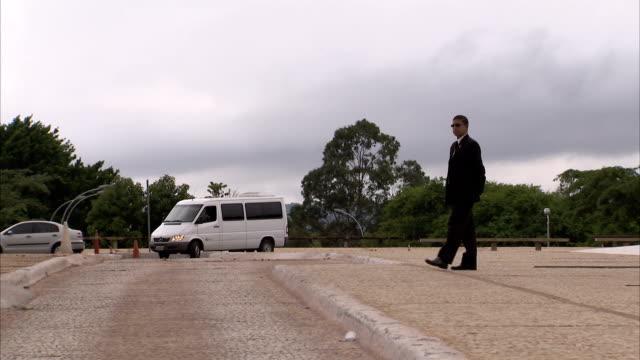 A security guard walks slowly across a car park towards an ice cream seller as a van approaches. Available in HD.