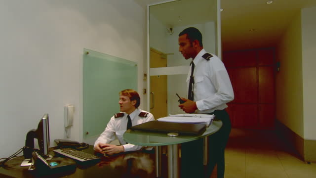 vídeos de stock e filmes b-roll de ws security guard watching computer screen then another guard enters and takes seat at desk while other man leaves office / london, england - sentar se