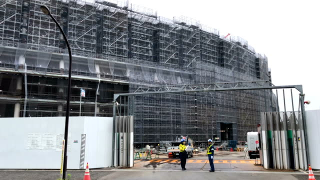 security guards ensure the road is clear as a truck leaves after making a delivery to the underconstruction new national stadium the main stadium for... - summer olympic games stock videos and b-roll footage