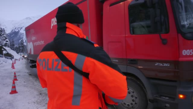 security guards monitoring a drive through to the world economic forum in davos, switzerland, on saturday, jan 19 police stands guard as a lorry... - wachpersonal stock-videos und b-roll-filmmaterial