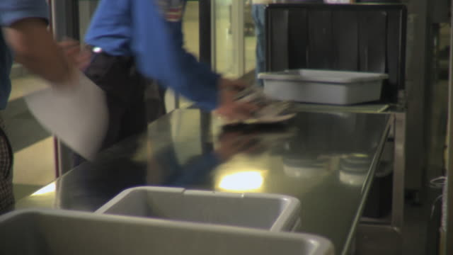 MS Security guards pushing belongings through x-ray machine in airport, Appleton, Wisconsin, USA