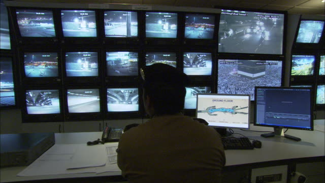 A security officer at a desk monitors images on a video wall.