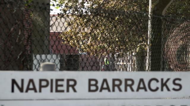 "security officer opens the entrance gate and a lorry enters behind a road sign that says ""napier barracks"", a former ministry of defence army base... - entrance sign stock videos & royalty-free footage"