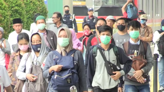 security officers check the temperature of commuters at the bogor train station and police officers inform people how to avoid the novel coronavirus... - indonesia stock videos & royalty-free footage