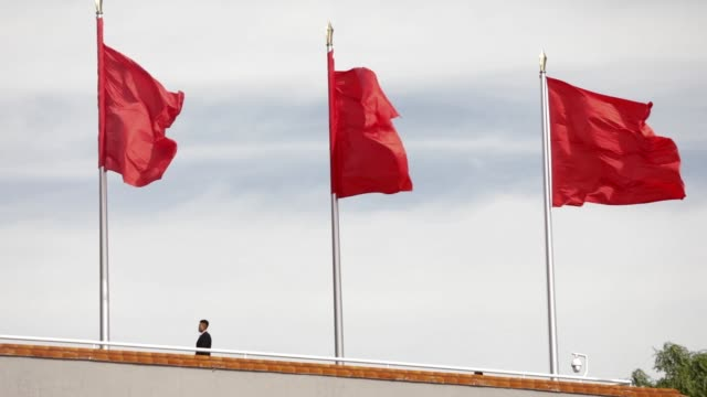 A security official stands guard under red flags at Tiananmen Gate in Beijing in Beijing China on Tuesday Sept 27 2016