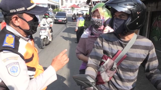 security officials hold check point across bogor city on april 15 as a prevention measures for the spread of the coronavirus people are urged to wear... - indonesia stock videos & royalty-free footage