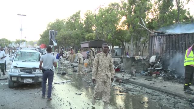 security officials inspect the site of a car bomb attack and wounded people are rushed to hospitals on may 24 2017 in mogadishu somalia at least five... - ソマリア点の映像素材/bロール