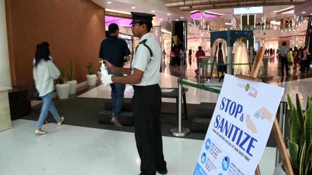 security personal providing hand sanitizers to arriving guests at the entrance of a shopping mall in kolkata as a part of precautionary measure... - uttar pradesh stock videos & royalty-free footage