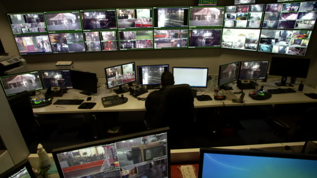 security personnel watching screens in street surveillance control room in downtown sydney with multiple screens on wall - spielsteuerung stock-videos und b-roll-filmmaterial