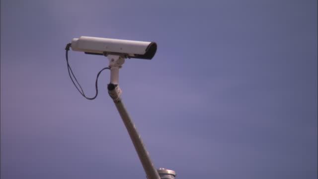 CU, Security surveillance camera on pole against clear sky
