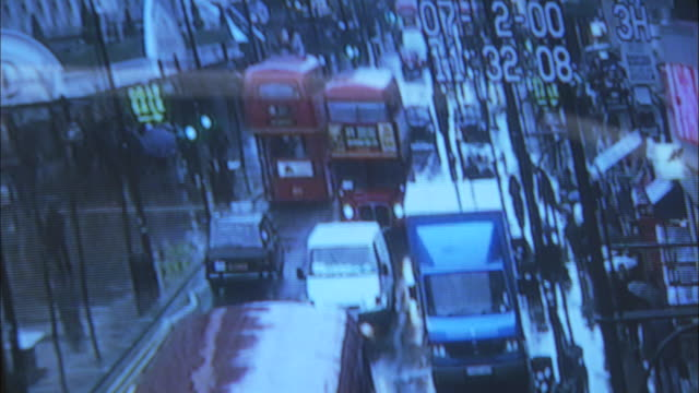 MS, Security surveillance monitor with view of London street with double decker buses traveling along with traffic, London, England