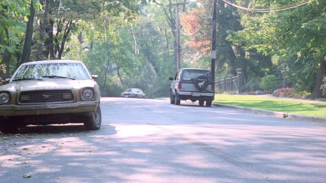 a bmw sedan approaches fast, stops suddenly, then speeds away. - stoppen stock-videos und b-roll-filmmaterial
