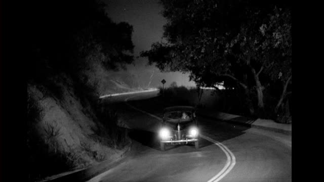 Sedan car drives along winding country road at night Car drives along winding country road at night on January 01 1940