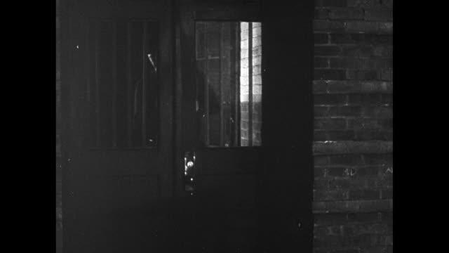 vídeos y material grabado en eventos de stock de sedan car pulling up to curb. policeman talking w/ night watchman, watchman back into building. man leaving two men in car, forcing open building... - ladrón de casas
