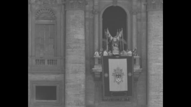 sedan chair bearing pope pius xi is set down on the balcony as he bestows blessings / pope blesses can see banner draped from balustrade / ws st... - catholicism stock videos and b-roll footage