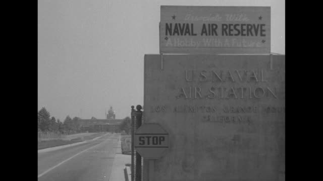 """sedan comes to a stop at a guarded gate with signs: """"naval air reserve, us naval station los alamitos orange county, california"""" - its driver is a... - guarding stock videos & royalty-free footage"""