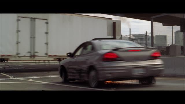 vídeos de stock, filmes e b-roll de ws sedan travels down freeway ramp, slides and crashes into the side of semi trailer truck - formato letterbox