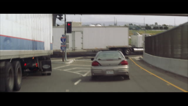 WS POV Sedan travels down freeway ramp, slides and crashes into the side of semi trailer truck
