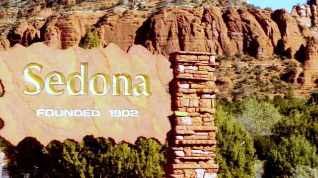 cu pan sedona city sign carved in stone to wide view of red rock mountains and chapel of holy cross church / sedona, arizona, usa - sedona stock videos & royalty-free footage